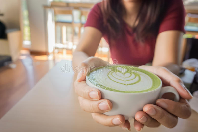 Woman holding cup of hot matcha green tea in her hands, sitting stock photo