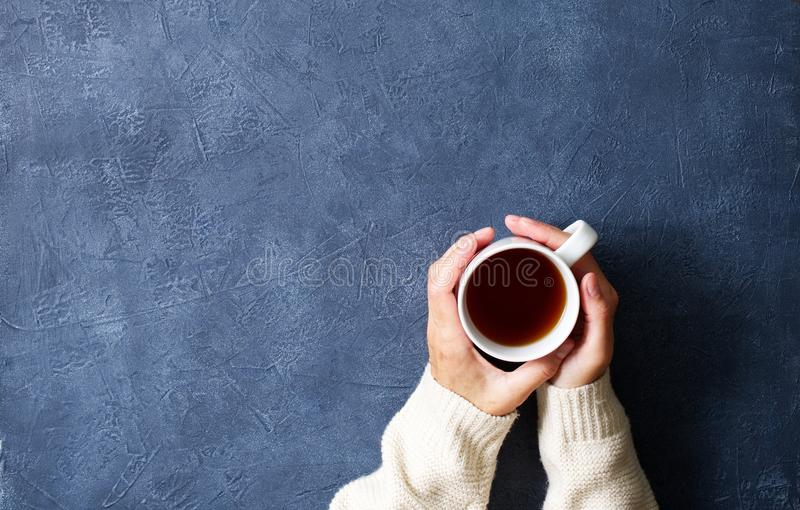 Woman holding cup of hot tea on dark blue table, hands in warm sweater with mug, winter morning concept, top view. Woman holding cup of hot tea on a dark blue stock photo