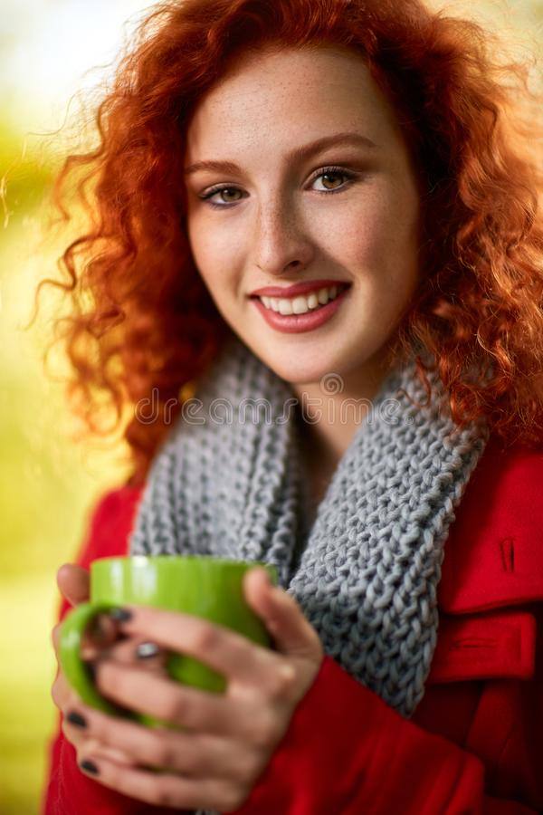 Woman holding cup of tea in park royalty free stock photo