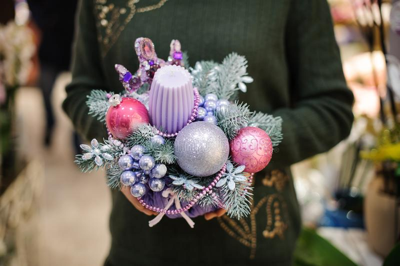 Woman holding a cute Christmas composition n pink and blue tones made of candle, fir tree and glass balls royalty free stock photo