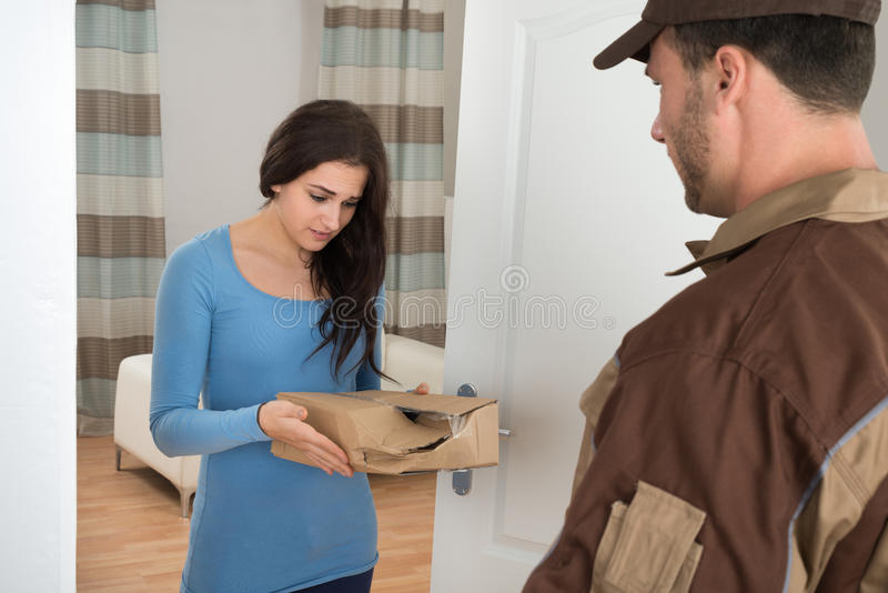 Woman holding damaged package from delivery man. Woman Shouting On Delivery Man For Damaged Package At Doorway royalty free stock image