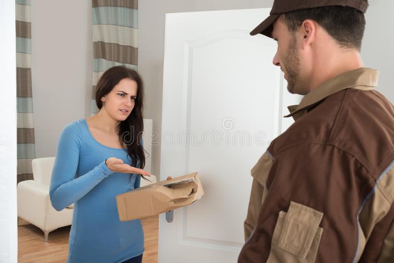 Woman holding damaged package from delivery man. Woman Shouting On Delivery Man For Damaged Package At Doorway royalty free stock photos