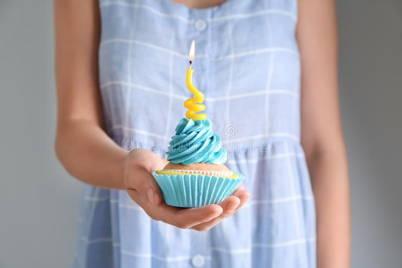 Woman holding delicious birthday cupcake with burning candle, closeup stock photo