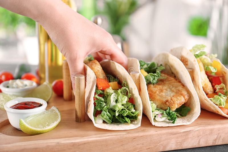 Woman holding delicious fish taco. In kitchen royalty free stock photo