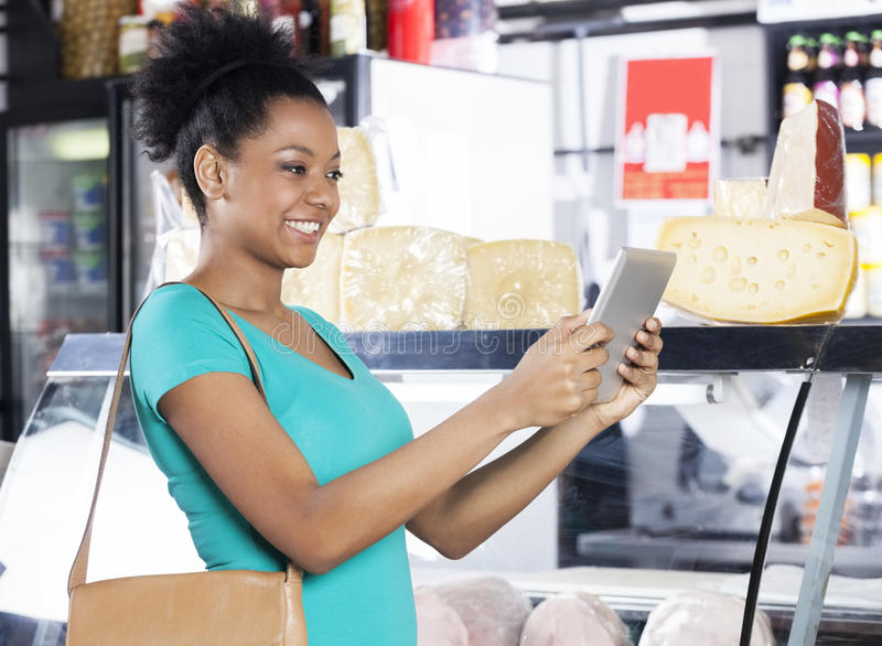 Woman Holding Digital Tablet In Grocery Store. Happy young woman holding digital tablet in grocery store royalty free stock photos