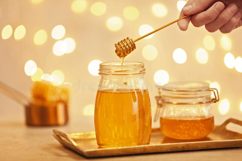 Woman holding dipper over jar with honey on table. Against blurred lights royalty free stock photography
