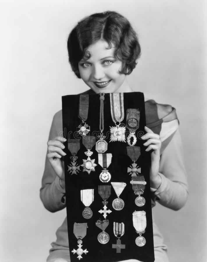 Woman holding display of medals. (All persons depicted are no longer living and no estate exists. Supplier grants that there will be no model release issues stock photography