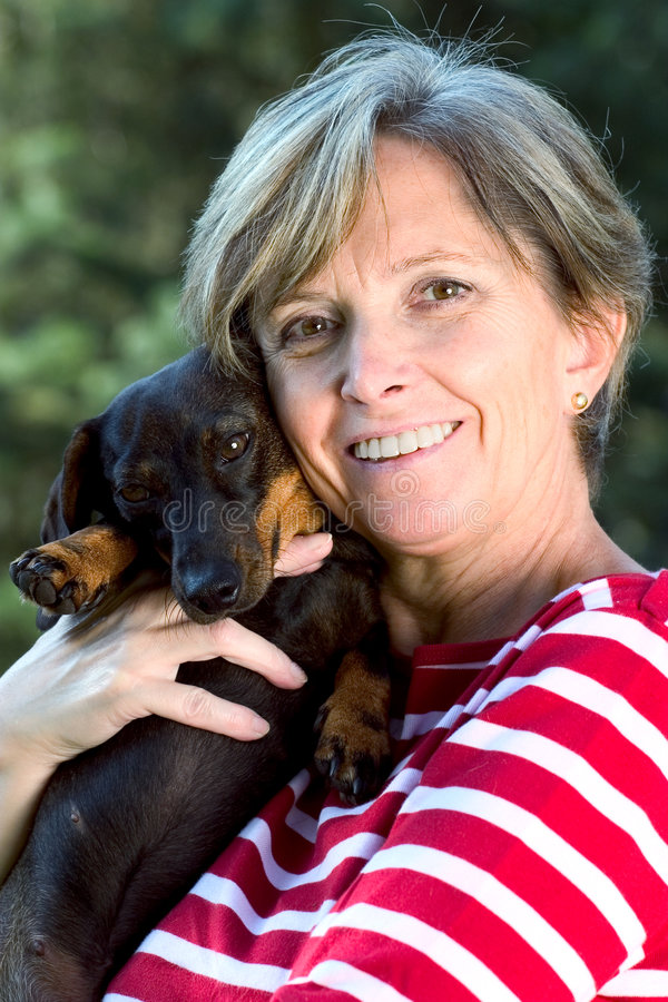Woman holding a dog stock photography