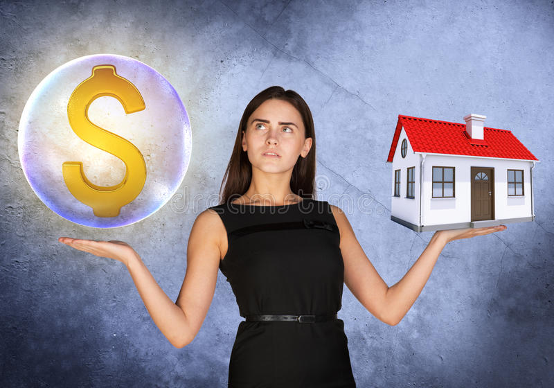 Woman holding dollar sign in bubble and house. Busineswoman holding dollar sign in big bubble and house on grey background royalty free stock photo