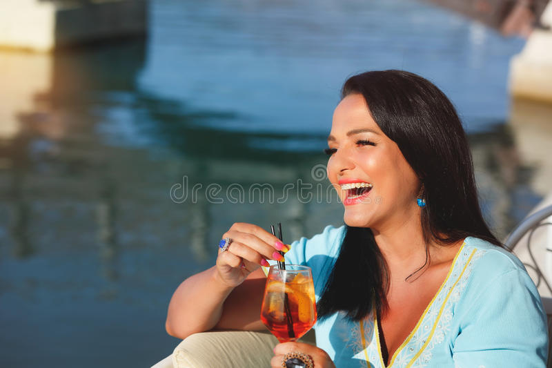 Woman holding a drink by the sea. Happy beautiful brunette woman having a drink in an outdoor cafe, selective focus stock photo