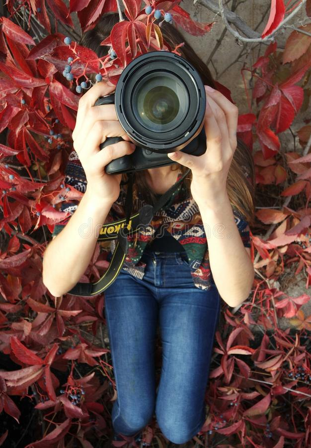 Woman Holding Dslr Camera Sitting On Red Leaved Plant Free Public Domain Cc0 Image
