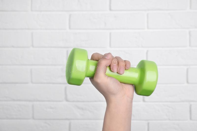 Woman holding dumbbell against brick wall. Home fitness. Woman holding dumbbell against brick wall, closeup. Home fitness stock photography