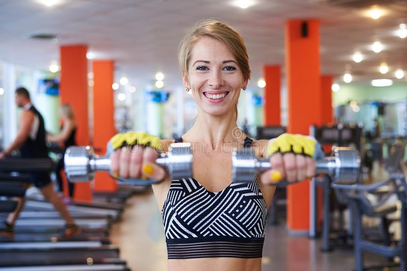 Woman holding dumbbells at gym royalty free stock photos