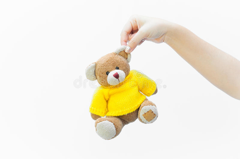 Woman holding ear brown teddy bear toy wear yellow shirts on white. Background royalty free stock images