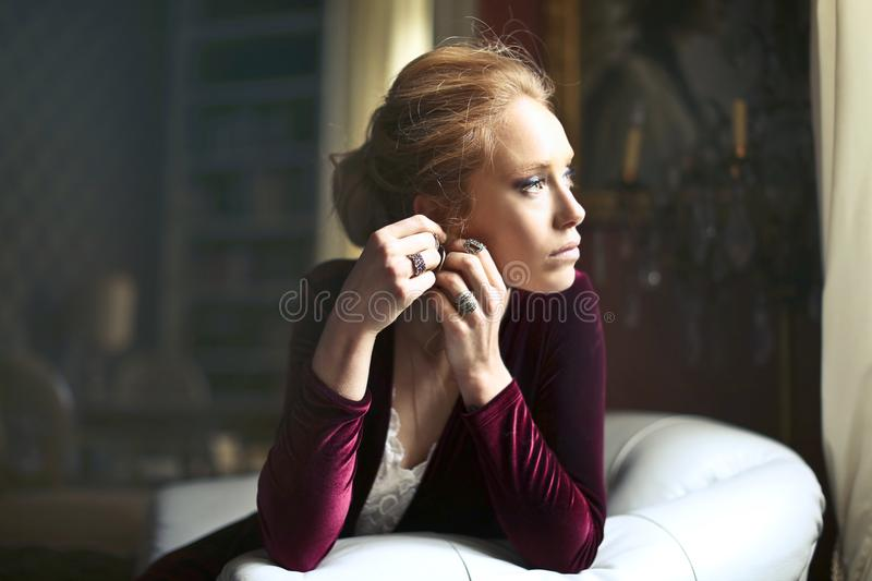 Woman Holding Ears Leaning Elbows on Sofa royalty free stock photography