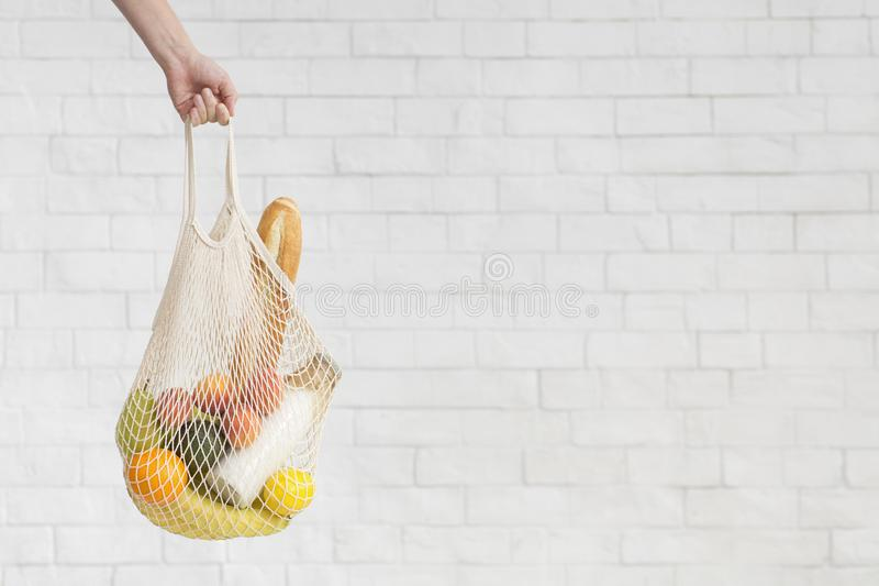 Woman holding Eco zero waste shopping bag with products for cooking stock photo