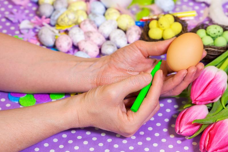 Woman holding egg near Easter decorations stock photo