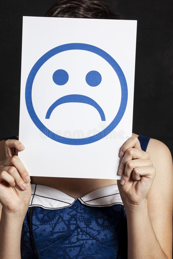 Woman holding emoticon - sadness stock photo