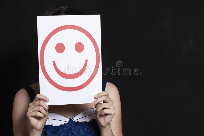 Woman holding emoticon smile. Black background - happy concept stock photo
