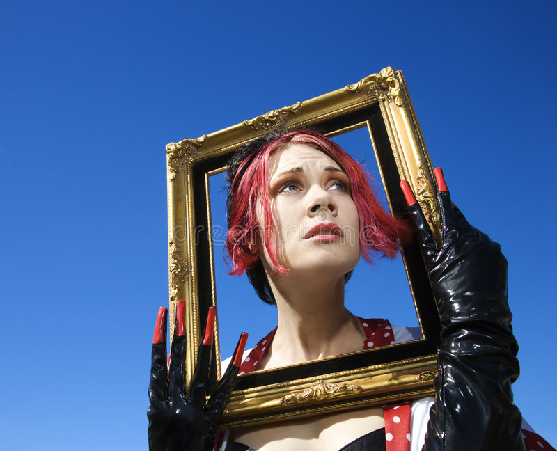 Woman holding empty frame around face. royalty free stock image