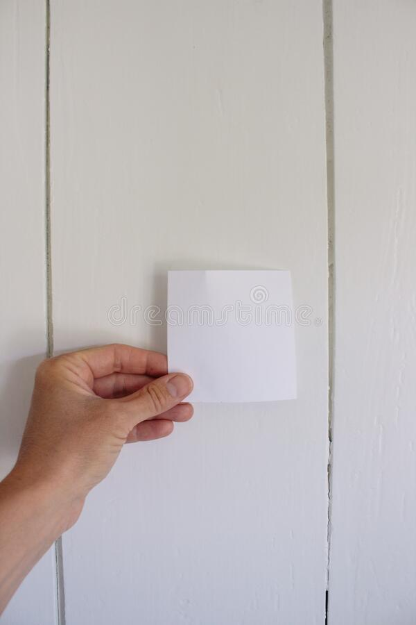 Woman holding an empty white paper. Young woman holding an empty white paper in her hands on a white wooden background, put your own wording on the space stock photography