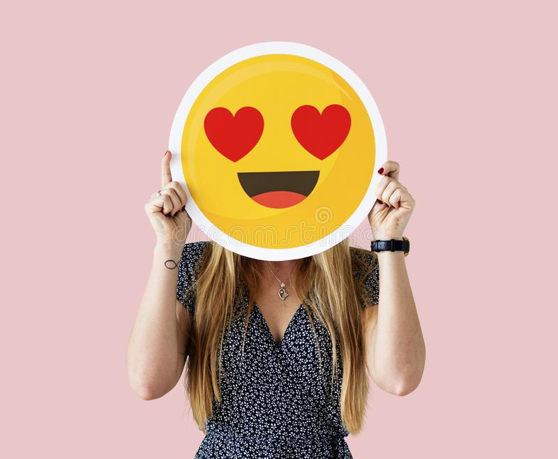 Woman holding a face emoji. Isolated stock images