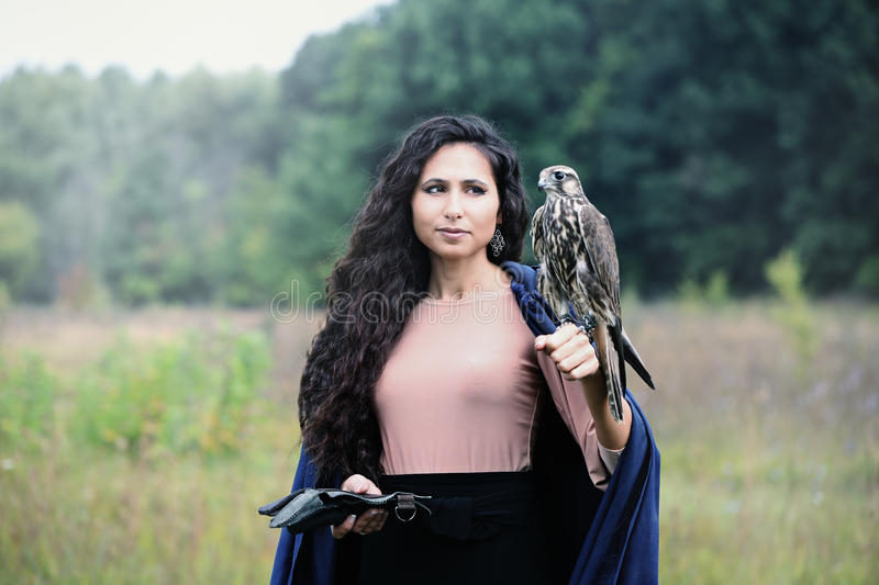Woman holding a falcon royalty free stock images