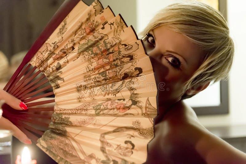 Woman is holding a fan stock image