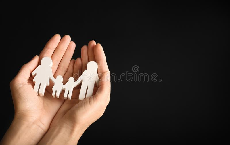 Woman holding figure of family in  on black background, closeup. Space for text. Woman holding figure of family in hands on black background, closeup. Space for royalty free stock images