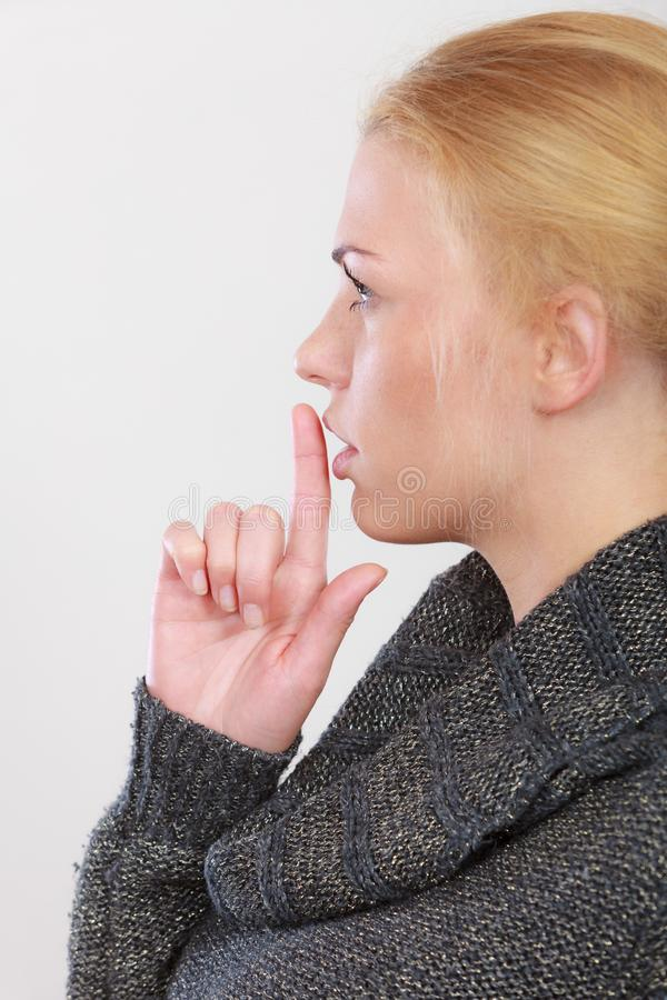 Woman holding finger close to lips, silence. Gestures, symbols of quiet concept. Profile portrait, blonde adult woman holding finger close to lips gesturing royalty free stock photos