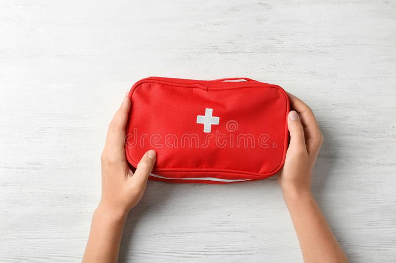 Woman holding first aid kit on wooden background royalty free stock image