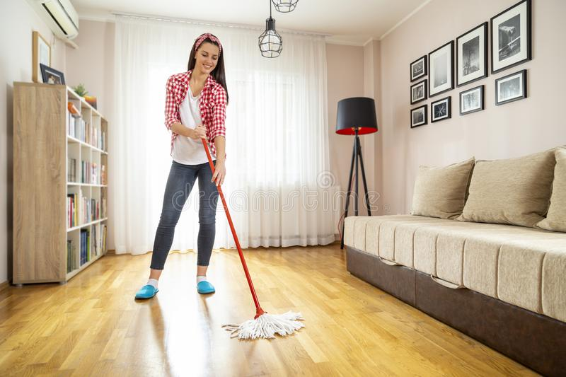 Sweeping the floor. Woman holding a floor wiper and wiping floor, doing house work and keeping the daily home hygiene stock images