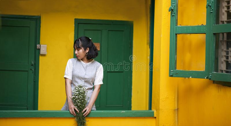 Woman Holding Flower Standing Behind Door stock photography