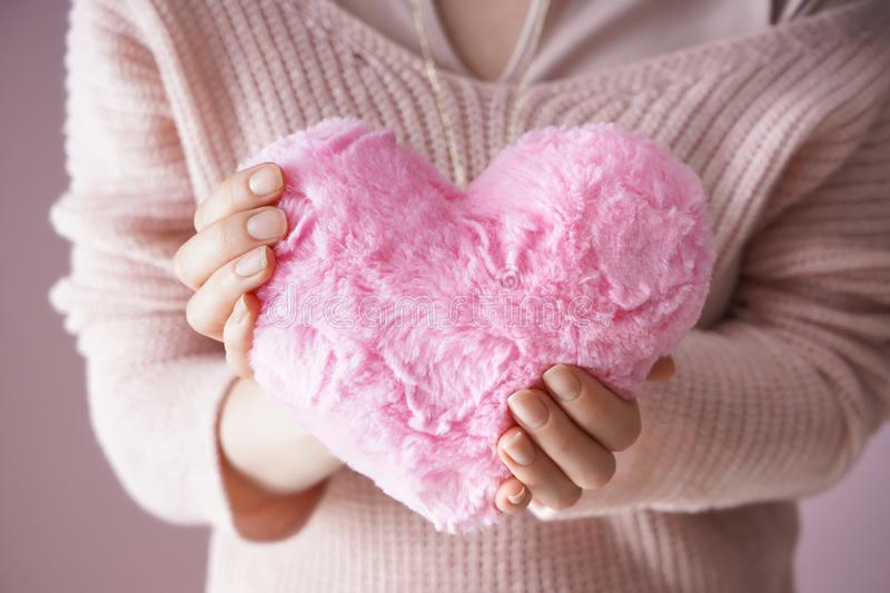 Woman holding fluffy heart-shaped pillow on color background, closeup royalty free stock photos