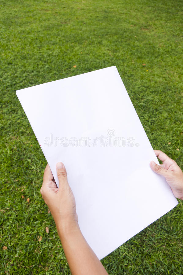 Woman is holding a flyer page, reading. For advertising purpose stock images
