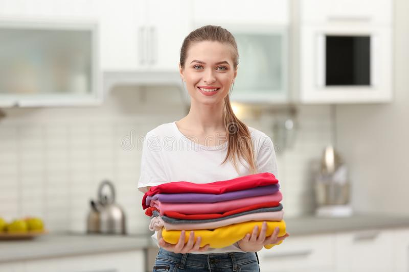 Woman holding folded clean clothes in kitchen stock images