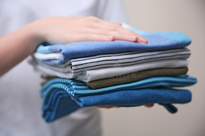 Woman holding folded clothes in hands, royalty free stock photography