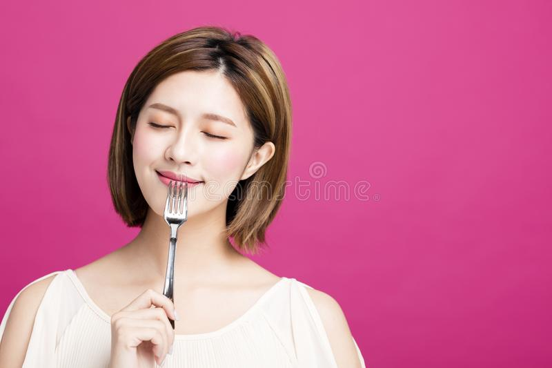 Woman holding fork and enjoy tasty food. Young woman holding fork and enjoy tasty food royalty free stock images