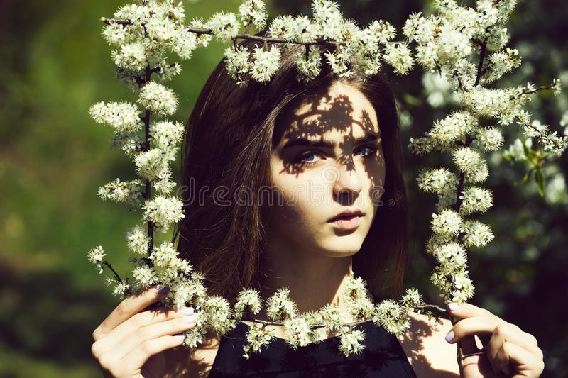 Woman holding frame of white, blossoming flowers. In spring garden on sunny day on blurred floral environment. Young beauty and nature royalty free stock photos