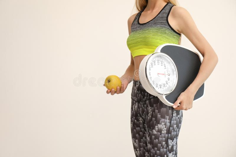 Woman holding fresh apple and scales. On light background. Healthy diet stock image