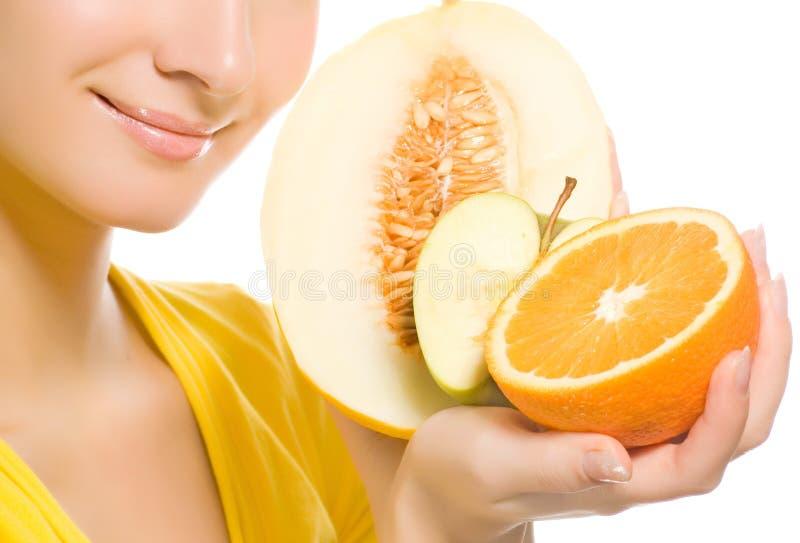 Woman holding fresh fruits. Beautiful young woman holding fresh fruits in her hands royalty free stock photography