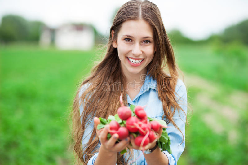 Download Woman Holding Fresh Radishes Stock Photo - Image of carefree, people: 25747868