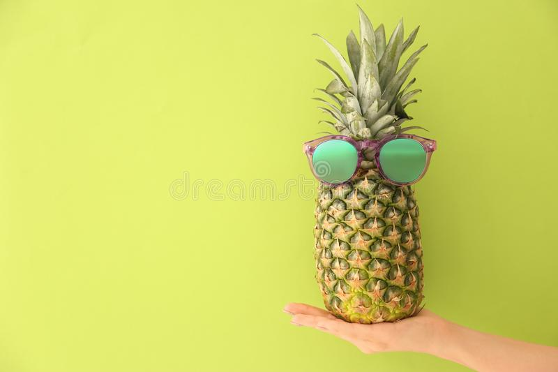 Woman holding fresh ripe pineapple with sunglasses. On color background stock images