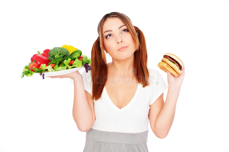 Woman holding fresh vegetable and burger royalty free stock photography