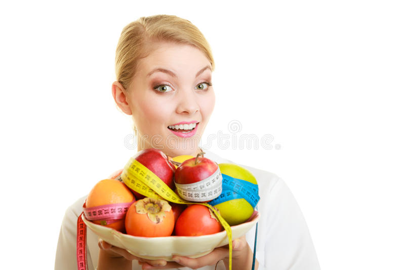 Woman holding fruits dietitian recommending healthy food. Closeup woman in white lab coat holding fruits and colorful measure tapes isolated. Doctor dietitian royalty free stock photo