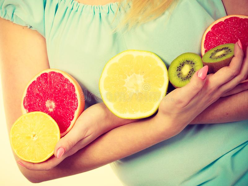 Woman holding fruits kiwi. orange, lemon and grapefruit stock images
