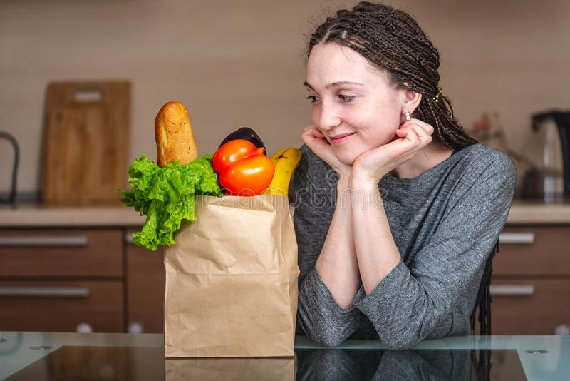 Woman holding full paper bag with products on the background of the kitchen. Fresh organic food for a balanced diet stock images