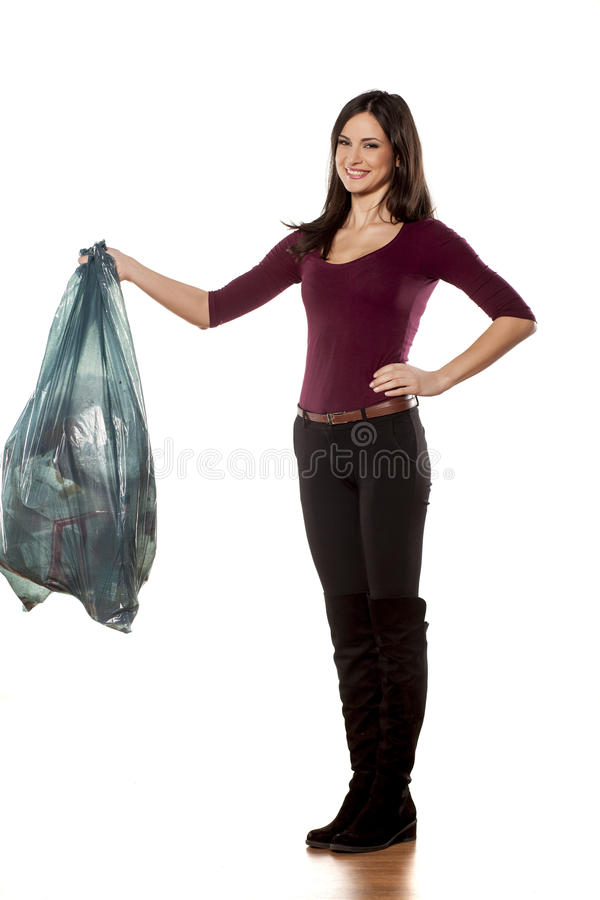 Woman holding garbage bag. Happy young woman holding garbage bag on white background stock photo