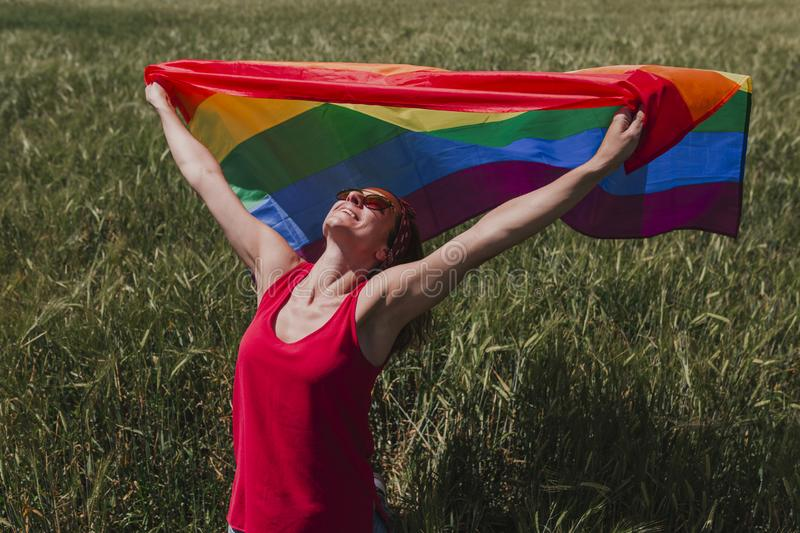 Woman holding the Gay Rainbow Flag on a green meadow outdoors. Happiness, freedom and love concept for same sex couples. LIfestyle royalty free stock photo