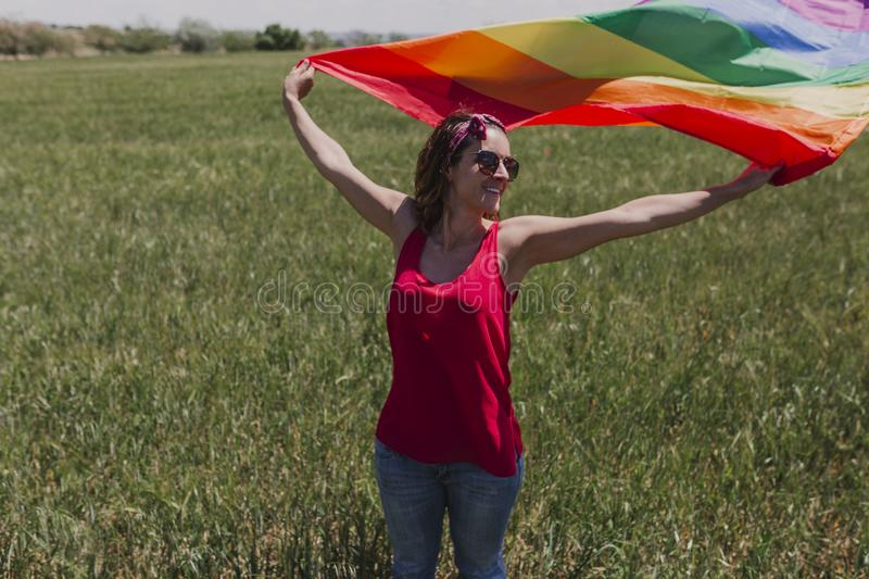 Woman holding the Gay Rainbow Flag on a green meadow outdoors. Happiness, freedom and love concept for same sex couples. LIfestyle. Outdoors royalty free stock image